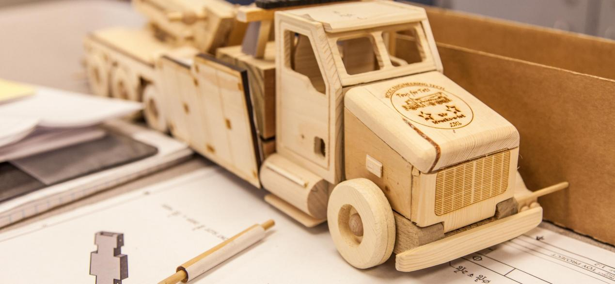 Image of a truck made out of individual wood parts designed by students, CAD drawings underneath truck